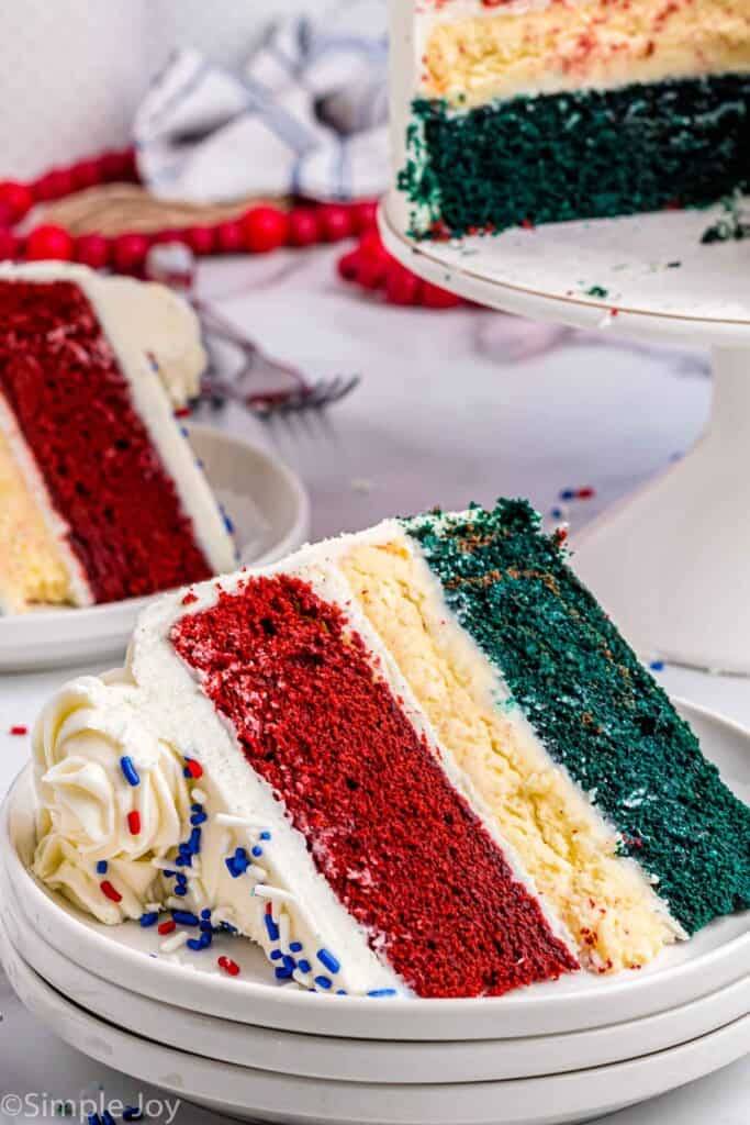 close up of a slice of red white and blue cake on three stacked white plates with the rest of the cake in the background