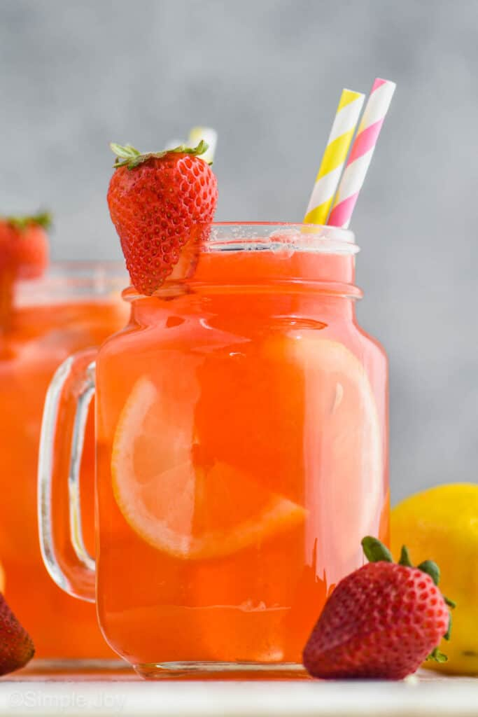 large glass of strawberry lemonade with a strawberry sliced and on the glass as a garnish
