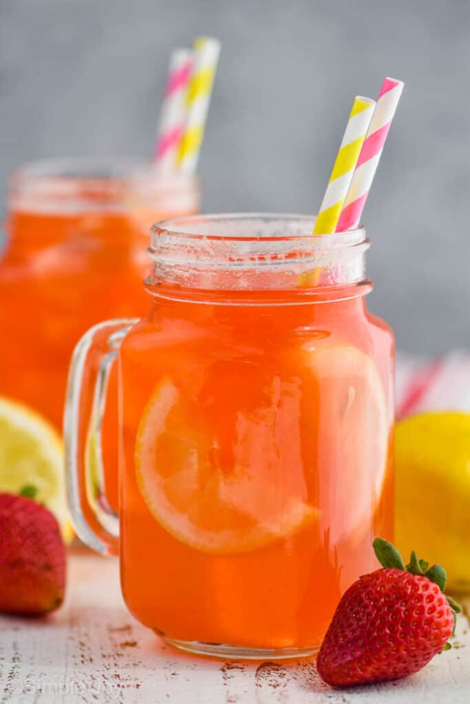large mason jar glass of strawberry lemonade with lemon slides inside the drink and served with paper straws