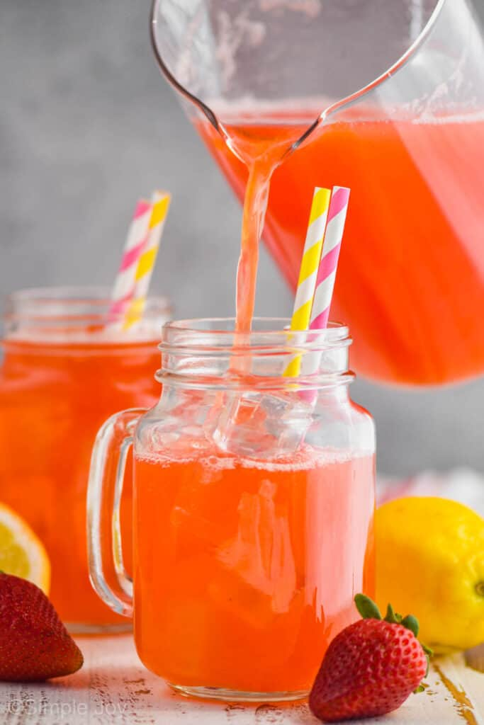 pitcher pouring strawberry lemonade recipe into a large glass mug