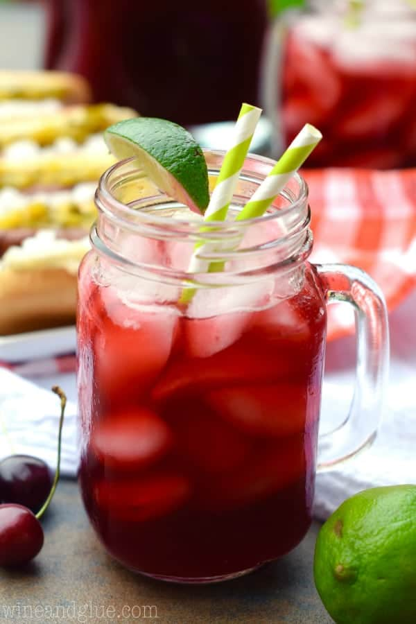In a mason jar glass, the Cherry Limeade has a dark red color with ice cubes and a slice of lime on the rim.