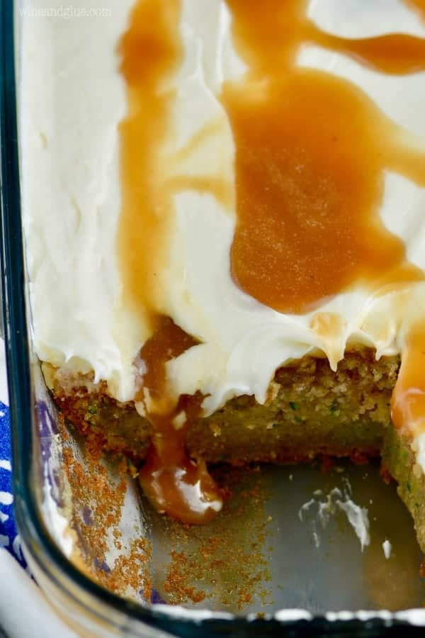 In a glass casserole dish, the Zucchini Poke Cake is topped with some white frosting and drizzled with caramel.