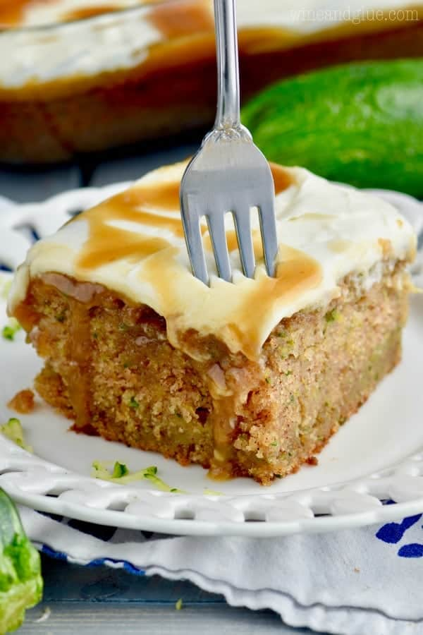 A fork digging into the Caramel Zucchini Poke Cake has a moist interior and drizzled with caramel.