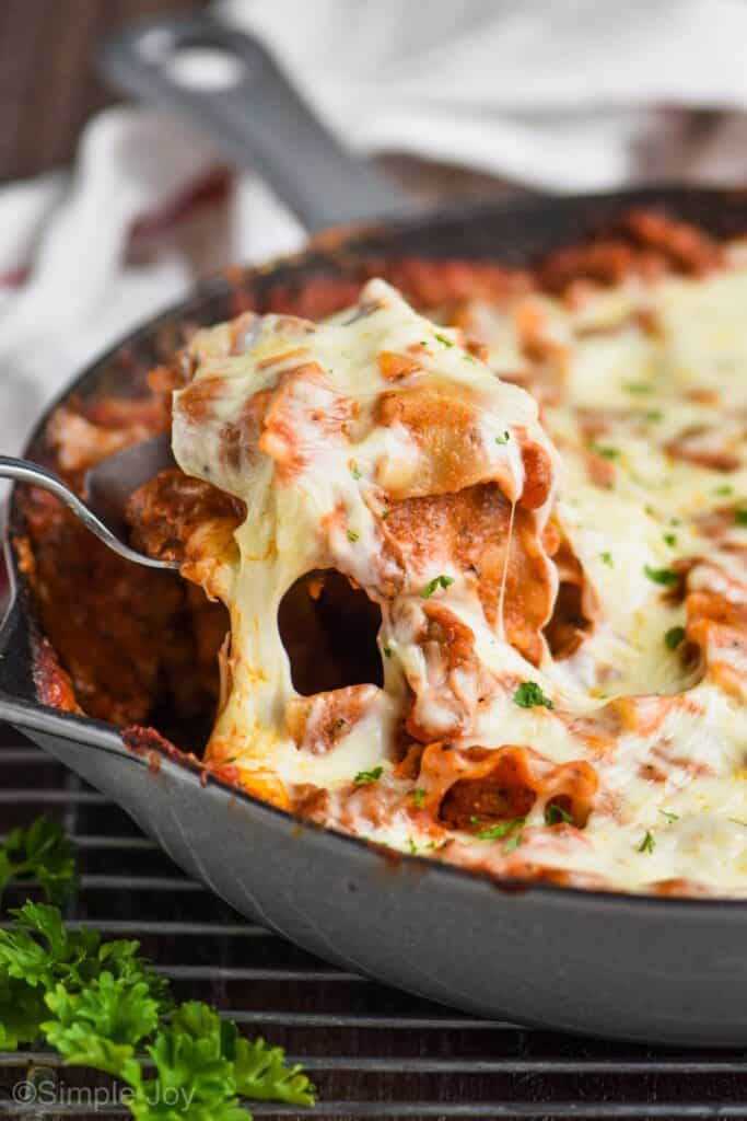 side view of a skillet and a spoon dishing up cheesy skillet lasagna
