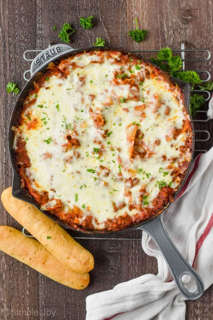 overhead of a gray skillet on a wood surface with skillet lasagna and two breadsticks next to it
