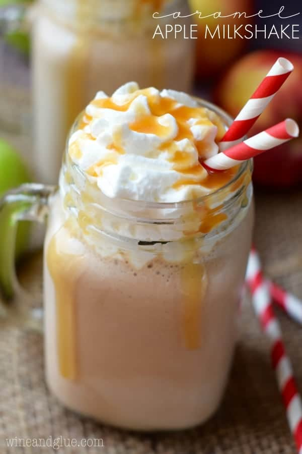 In a mason jar glass, the Caramel Apple Milkshake is topped with whipped cream and caramel dripping down the sides.