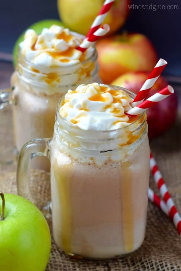 In two glass mason jars, the Caramel Apple Milkshakes are topped with whipped cream and dripping with caramel.
