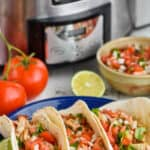 three tacos on a blue plate in front of a crockpot