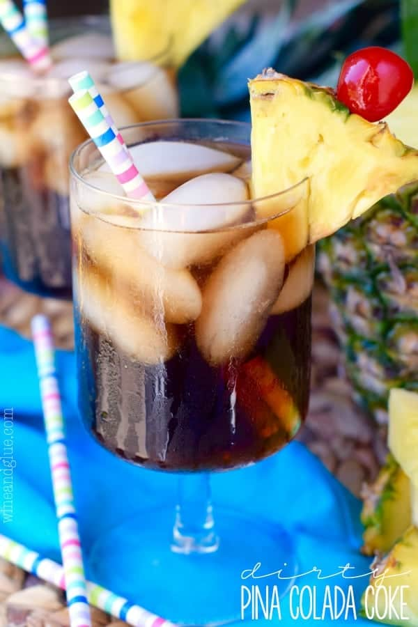 In a glass, the Dirty Pina Colada Coke has two paper straws and rimed with a sliced pinapple and cherry.