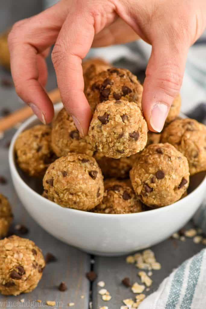 fingers setting down peanut butter energy balls into a bowl