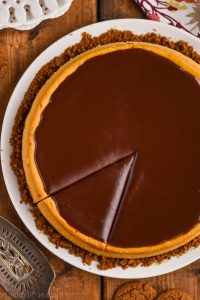 overhead view of a pumpkin cheesecake covered in chocolate ganache with one piece cut into