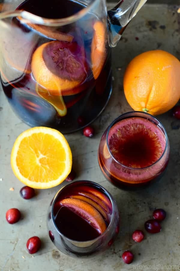 An overhead photo of the Cranberry Orange Sangria in two tumbler glasses and a pitcher with sliced oranges in the shape of a circle.