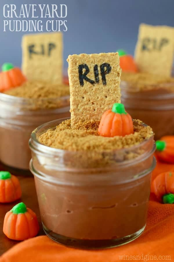 In a small mason jar, the Pumpkin spice Chocolate Pudding is topped with crushed graham cracker, a pumpkin candy, and a stick of a graham cracker with the letter RIP.