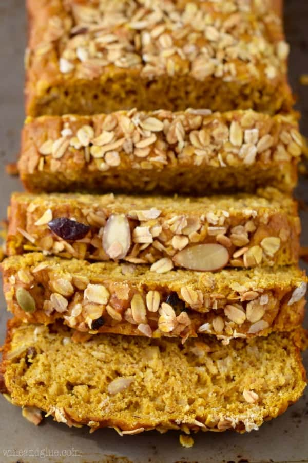 The Muesli Pumpkin Bread are cut into slices and the top of the bread is sprinkled with different types of seeds and nuts.