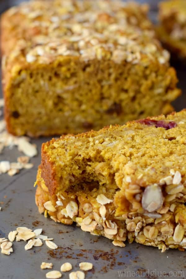 Slices of the Muesli Pumpkin Bread showing the pumpkin colored bread topped with oats, almonds, sunflower seeds, and more.