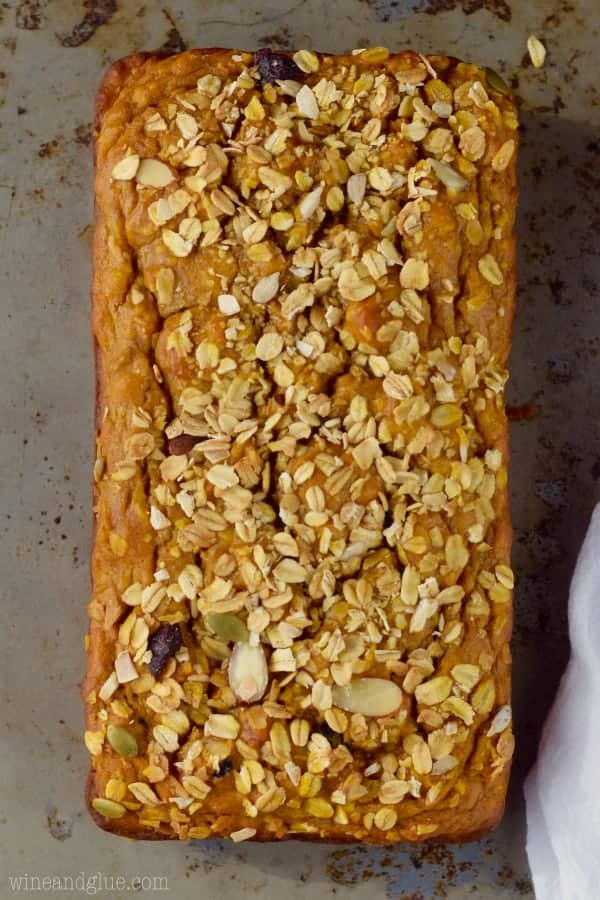 An overhead photo of the Muesli Pumpkin Bread showing the oats, sliced almonds, sunflower seeds, and more nuts sprinkled on top.