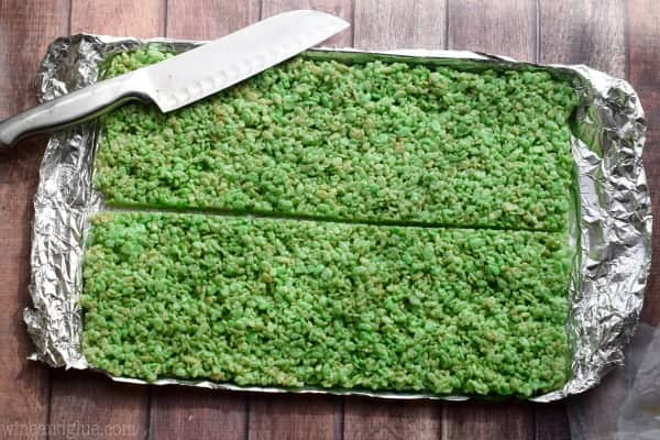 An overhead photo of a the green Rice Krispies on a baking sheet cut horizontally in the middle.