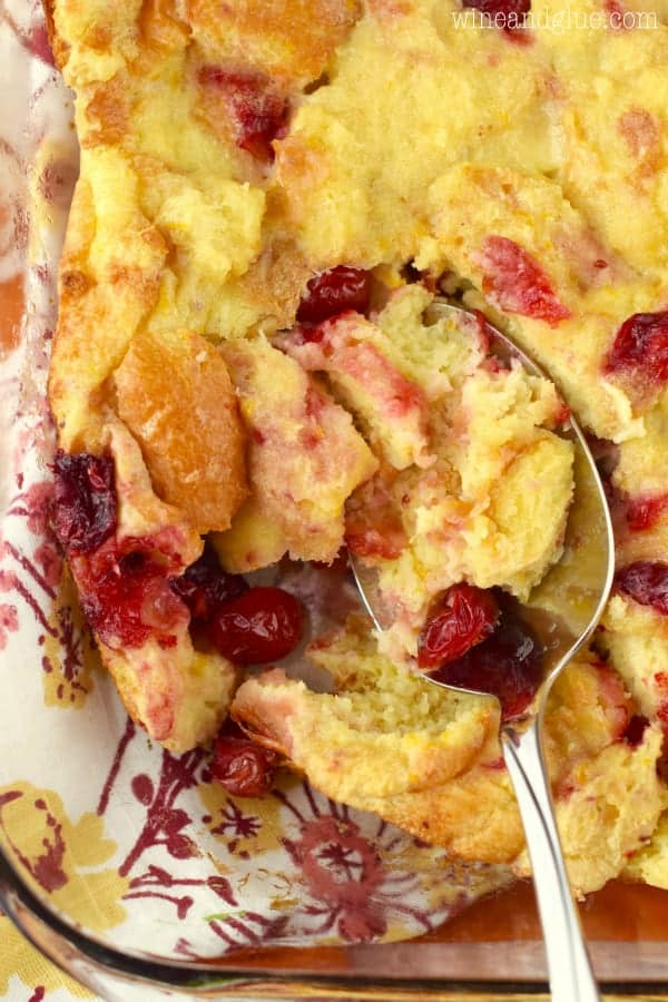 In a glass casserole dish, a spoon is scooping into the Cranberry Orange Bread Pudding showing the speckles of red from the cranberries.