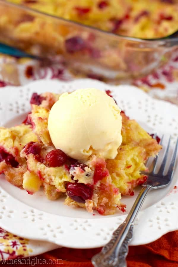 On a white plate, the Cranberry Orange Bread Pudding has a scoop of a vanilla ice cream on top.