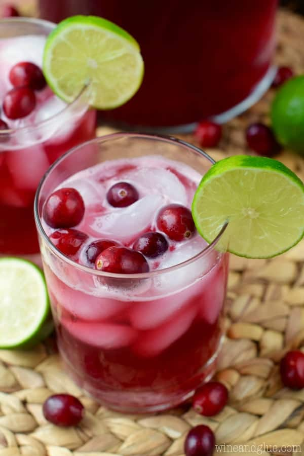 Two glasses of the Cranberry Beergaritas with a dark maroon color with ice cubes, whole cranberries, and a slice of lime on the rim.