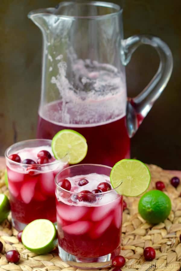 Two glasses of Cranberry Beergaritas in front of the large pitcher.