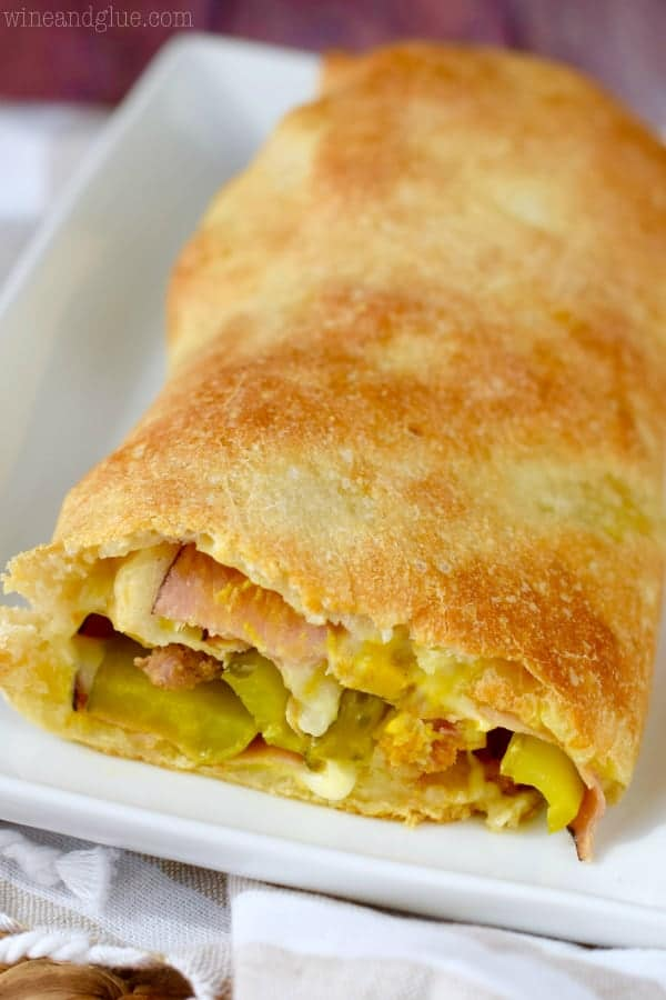 The Cuban Stromboli is cut showing the ham, Italian Sausage, pickles, Swiss cheese, and mustard.