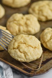fast and easy drop biscuits being picked up by a metal spatula off a baking sheet