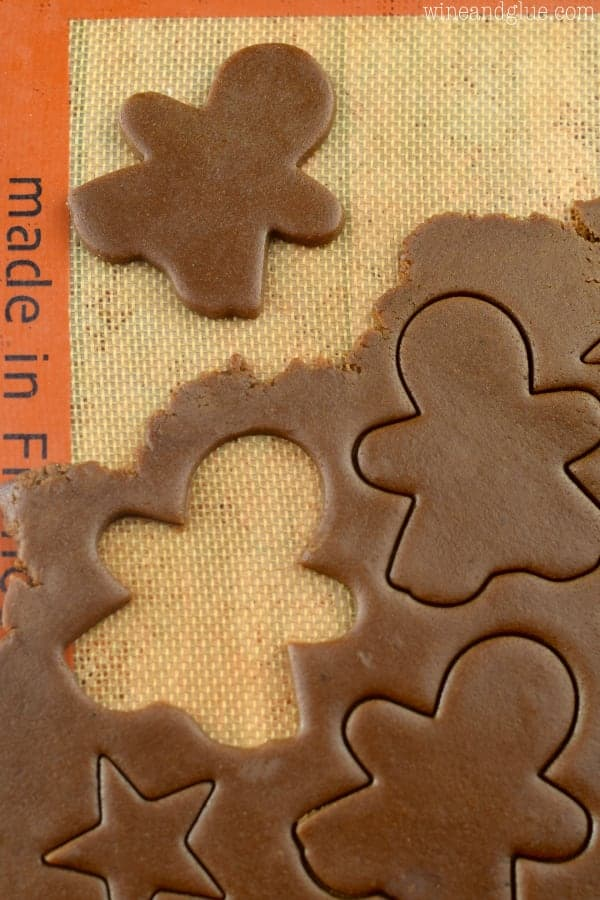 The Gingerbread Cookie Dough is rolled out flat and little shaped people are cut out of the dough.