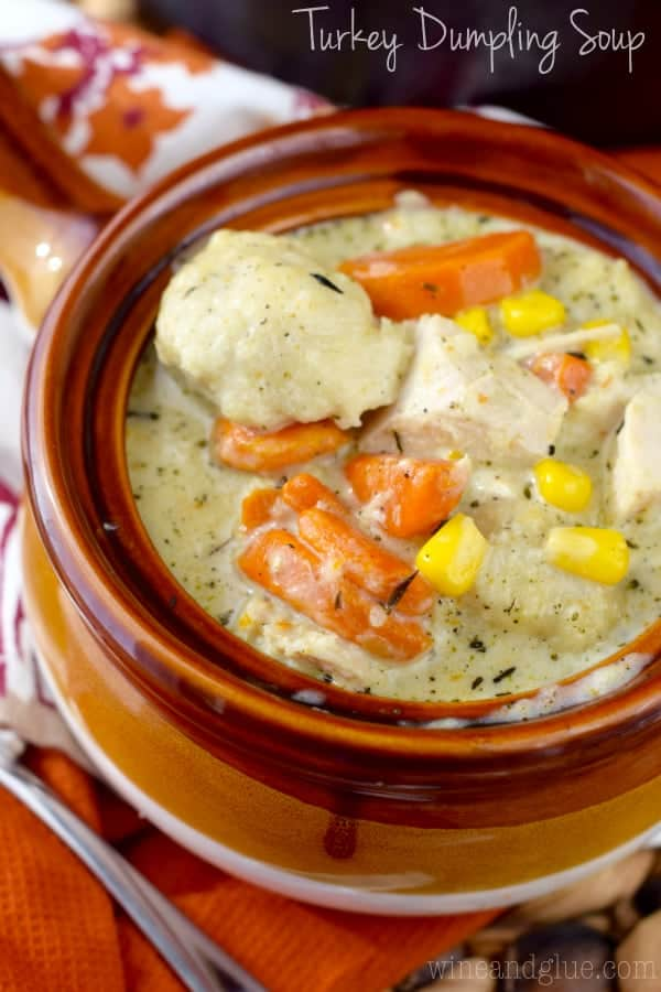 In a brown ceramic bowl, the Turkey Dumpling Soup has chunks of turkey, balls of dumpling, slices of carrots, and corn in a creamy broth.