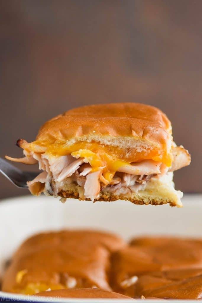 a bacon ranch turkey slider being pulled out of a baking dish of other sliders with melted cheddar cheese and turkey visible