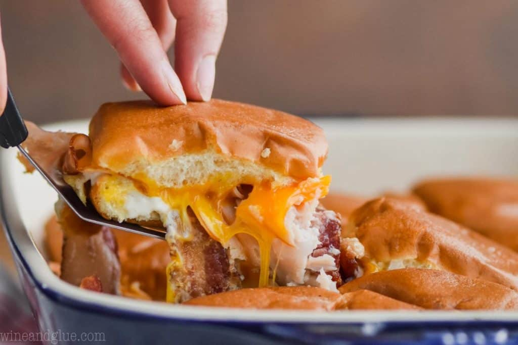 landscape style photo of a turkey slider coming out of the pan with cheddar cheese, bacon, and ranch dressing visible