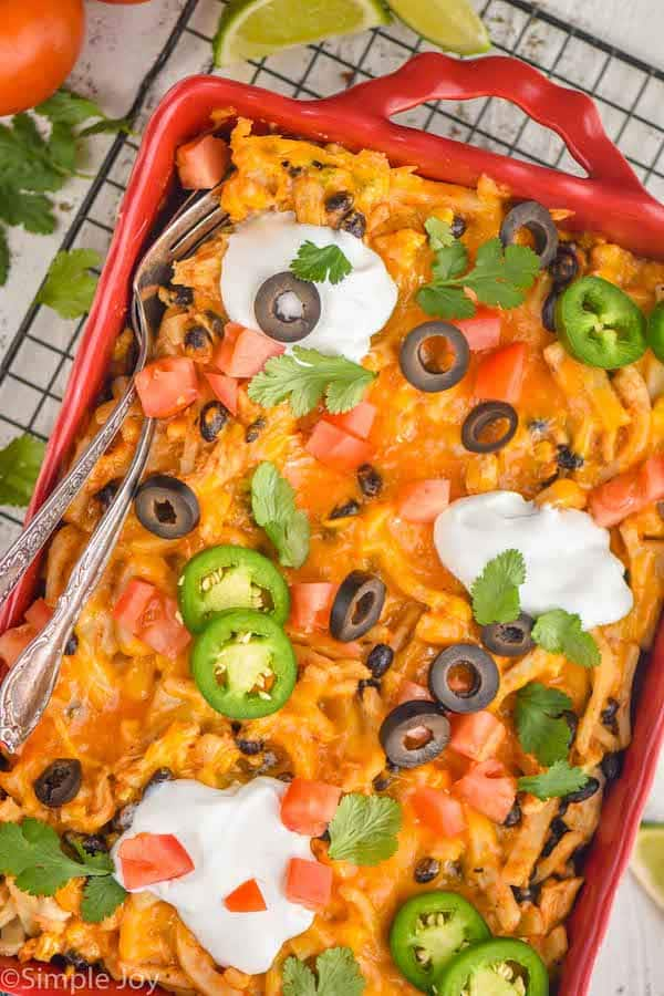 overhead view of a chicken taco casserole in a red baking dish garnished with sour cream, jalapeños, olives, and cilantro