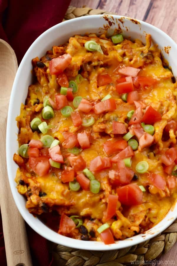 Chicken Taco Casserole features brightly colored tomatoes and green onions on top.