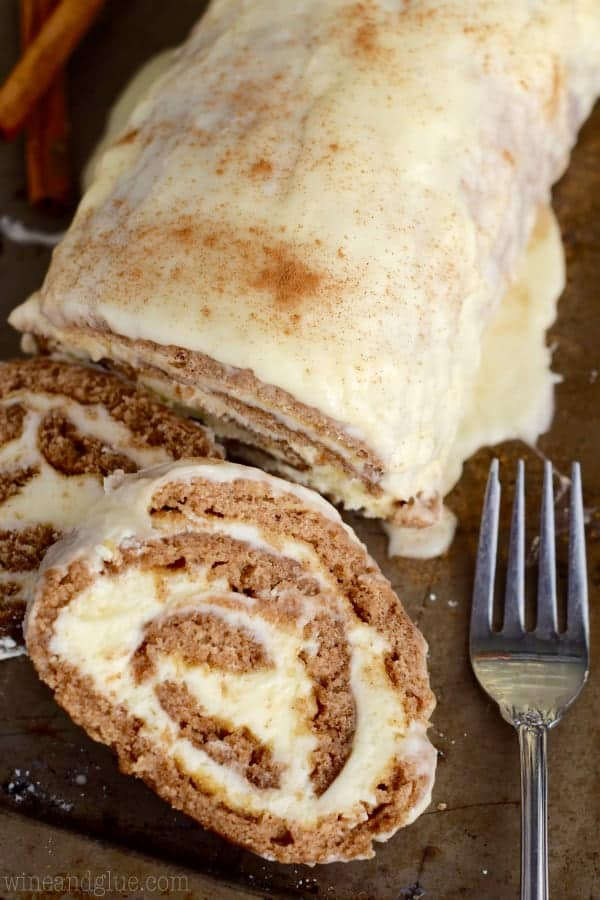 An overhead photo of two slices of the Cinnamon Cake Roll next to the cake roll showing the buttercream filling and topped with a glaze.