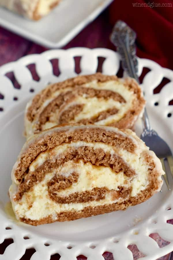 On a white plate, two slices of the Cinnamon Cake Roll is rolled up with a buttercream frosting in a spiral shape.