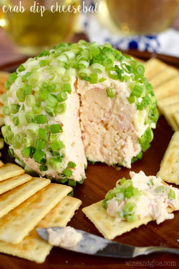 Surrounded by crackers, the Crab Cheese Ball has a large slice cut out and topped with chives.