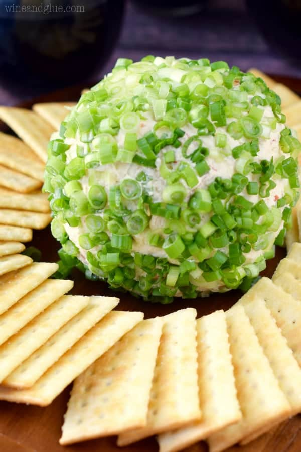 The Crab Dip Cheeseball has scallions covering the outside and surrounded by club crackers.