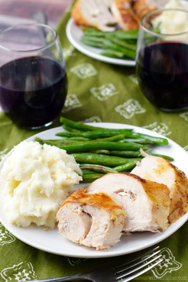 On a white plate, a hefty scoop of the Easy Ranch Potatoes is a side dish with green beans for a chicken entree.
