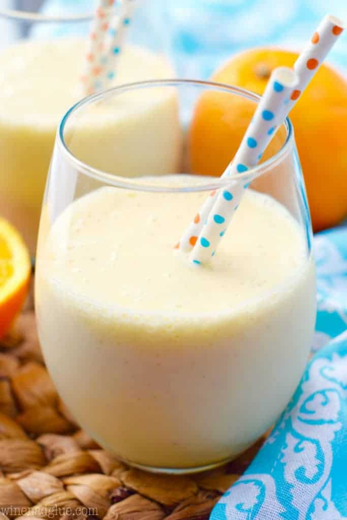 In a glass, the Orange Colada Smoothie has a pastel yellow color with two paper straws.