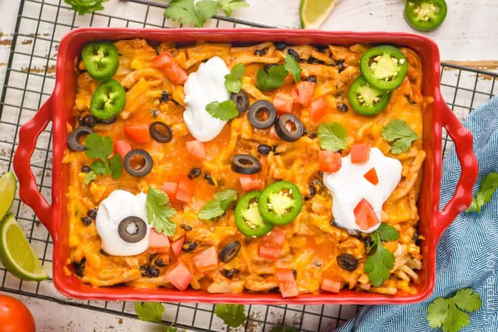 overhead of a taco casserole in a baking dish garnished with taco toppings