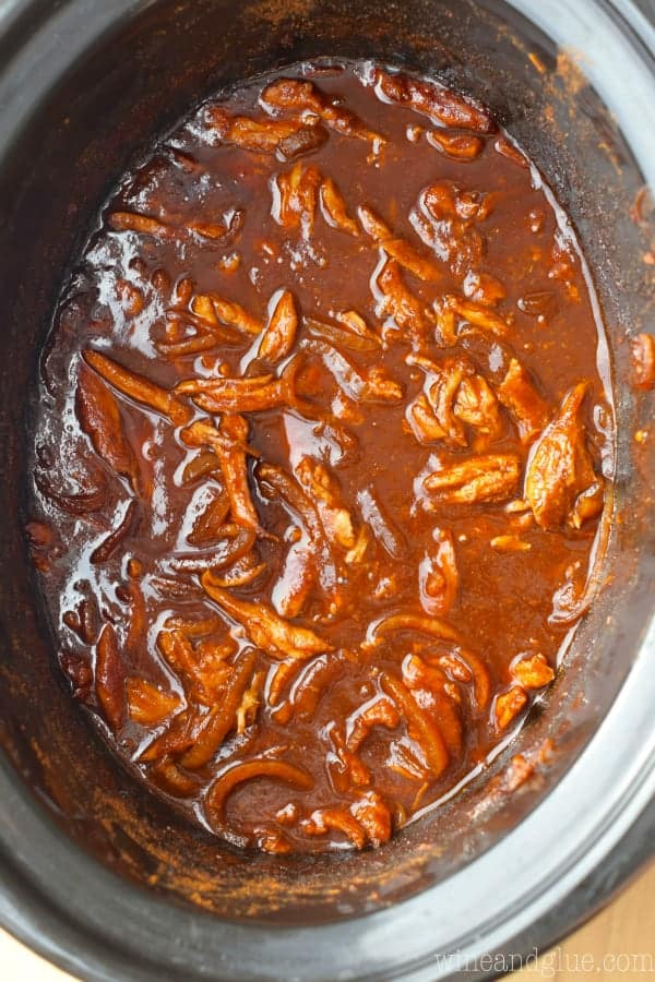 An overhead photo of crockpot with shredded chicken and BBQ sauce.