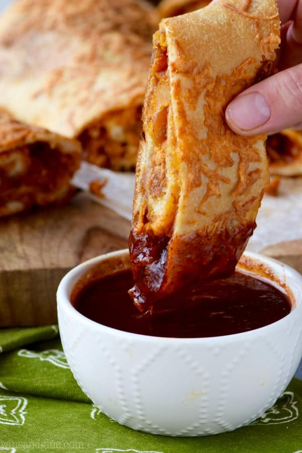 A slice of BBQ Chicken Pizza Roll is being dipped into BBQ sauce.