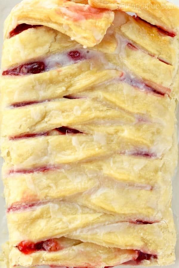 An overhead photo of the Cherry Almond Braid that has some cherry filling oozing out and glazed with some icing.