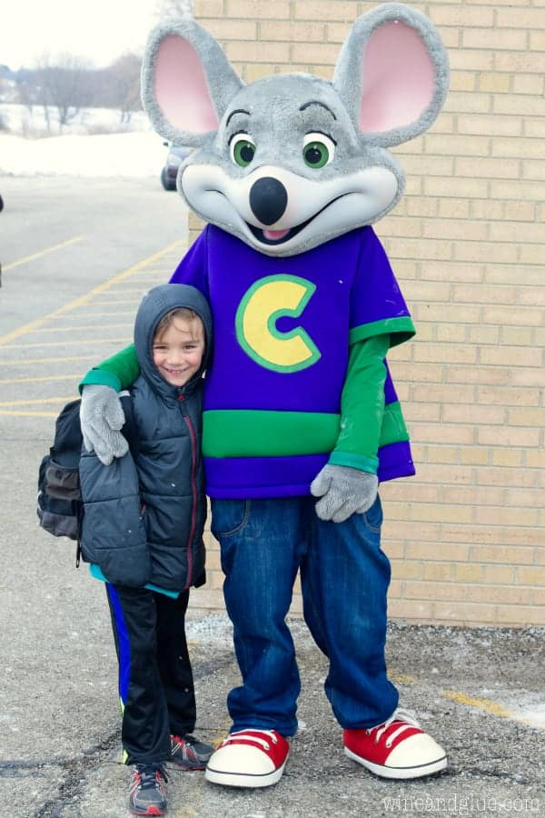A little boy taking a picture next to Chuck E. Cheese.