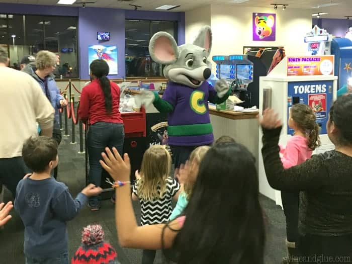 A picture of little children greeting Chuck E. Cheese.