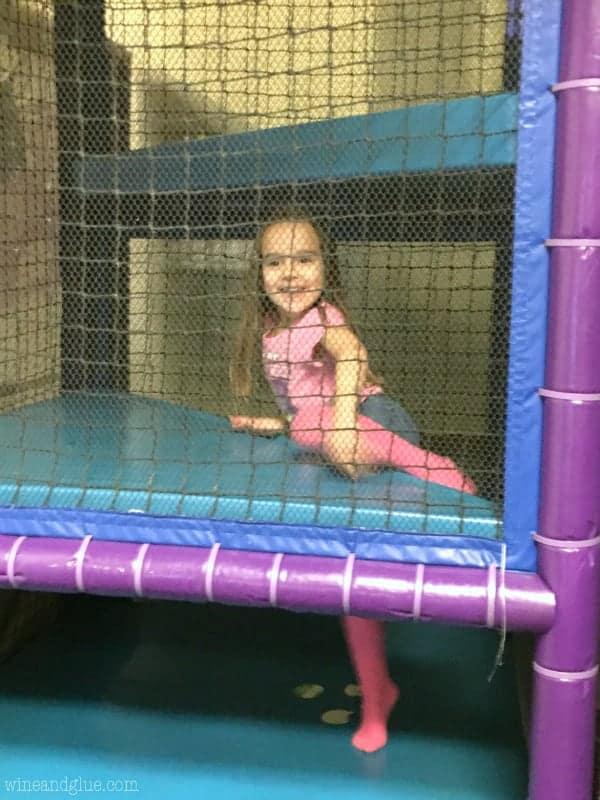A little a girl climbing up a playground.