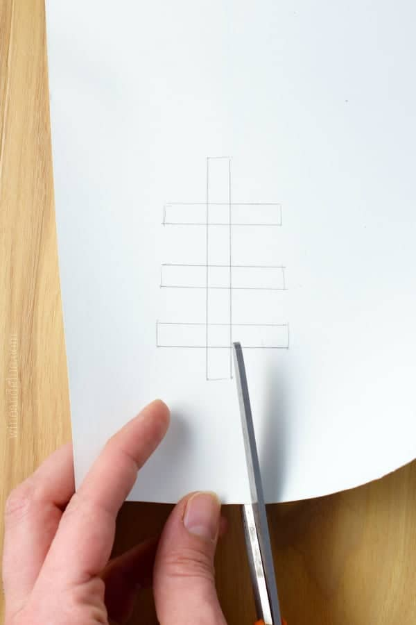 A woman cutting out the vertical line with three horizontal lines which is the football seam.
