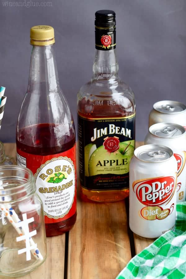 A photo of the ingredients of the Super Bowl Slammers (Grenadine, Apple Bourbon, and Dr. Pepper).