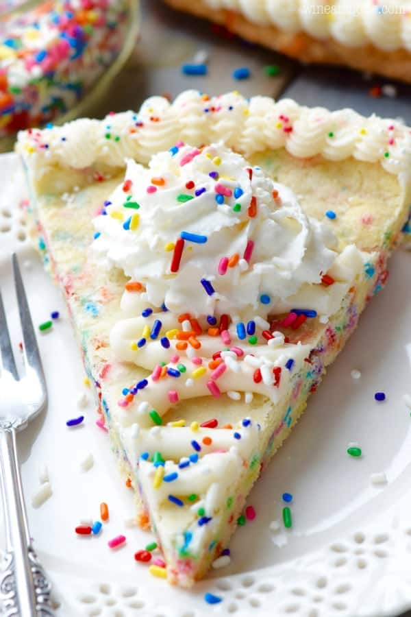 On a white plate, the Funfetti Cookie Cake has white frosting on the edge of the cookie cake with a star tip and whipped cream in the middle topped with rainbow sprinkles.