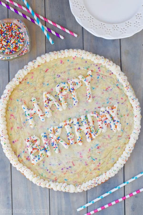 An overhead photo of the Funfetti Cookie Cake with white frosting on the side and the words of Happy Birthday in the middle topped with rainbow sprinkles.